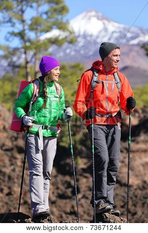 Hikers people hiking - healthy active lifestyle. Hiker couple hiking in beautiful mountain nature landscape. Woman and man hikers walking during hike on volcano Teide, Tenerife, Canary Islands, Spain.