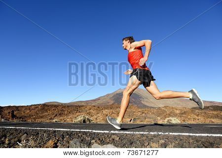 Sport running man - male runner training outdoors sprinting on mountain road in amazing landscape nature. Fit handsome jogger working out for marathon outside in summer.