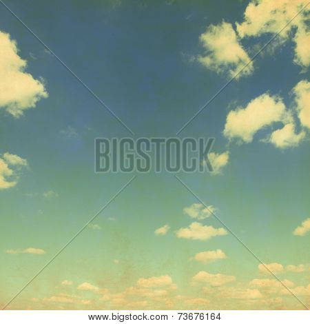 Blue sky with sparse clouds in grunge style.