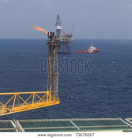 Jack Up Drilling Rig, Flare Boom, And Crew Boat In The Middle Of The Sea