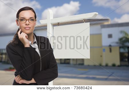 Attractive Serious Mixed Race Woman In Front of Vacant Retail Building and Blank Real Estate Sign.