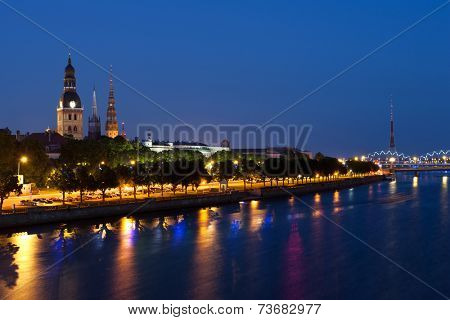 Skyline of Riga seen across the river Daugava after the sunset. Three church towers in the picture are the Riga Dome cathedral,  St. Saviour's Church and St. Peter's church.
