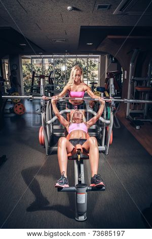 Beautiful girls in fitness club out exercise with a bar in the gym Bar Bench Press