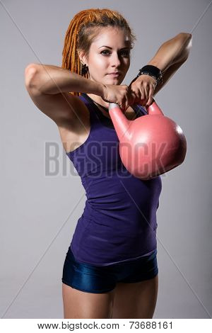 Portrait Of Young Attractive Female Doing Kettle Bell Exercise On Grey Background.