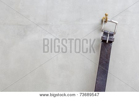 The Black Leather Belt Hanging On The Hanger With Exposed Concrete Wall.