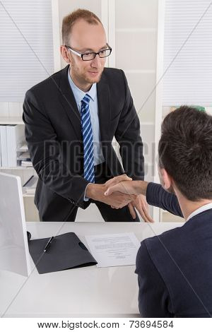 Smiling manager says hello to a candidate in a job interview with handshake.