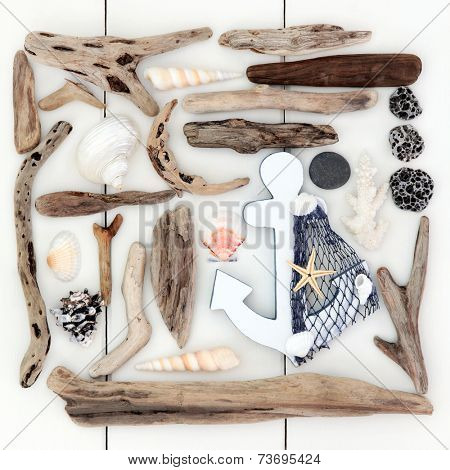 Beach and seaside shells, driftwood, pebbles and decorative anchor over wooden white background.