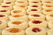 image of shortbread  - Rows of shortbread cookies filled with peach and raspberry jam on wax paper - JPG
