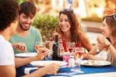 picture of food groups  - Group Of Young Friends Enjoying Meal In Outdoor Restaurant - JPG