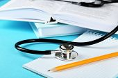 pic of medical supplies  - Medical stethoscope with notepad and books on blue background - JPG