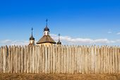 picture of log fence  - Wooden church with three steeples and crosses is behind a fence of logs against the sky - JPG
