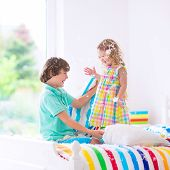 picture of pillow-fight  - Two children happy laughing boy and cute curly little girl having fun at pillow fight with feathers in the air jumping laughing and giggling in a white bedroom with colorful bedding