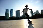 picture of skateboarding  - woman skateboarder legs skateboarding at sunrise city - JPG