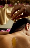 image of essential oil  - essential oil poured on a female back in spa centre - JPG