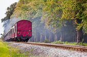 picture of caboose  - Back of a steam train with a red rail car at the end on a track through beautiful landscape - JPG