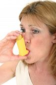 foto of breather  - Woman demonstrates the use of an asthma or bronchial inhaler - JPG