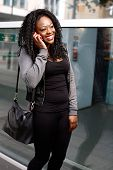 picture of vivacious  - Laughing young woman chatting on a mobile phone or cellphone as she stands on a sidewalk on an urban street smiling with happiness at the conversation - JPG
