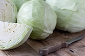 stock photo of cruciferous  - Cabbage with knife on old wooden desk - JPG