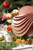stock photo of kumquat  - Christmas dinning table with glazed roasted ham with tomatoes herbs and kumquats - JPG