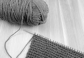 pic of garter  - Close up of ball of wool with length of garter stitch on a knitting needle on wood - monochrome processing