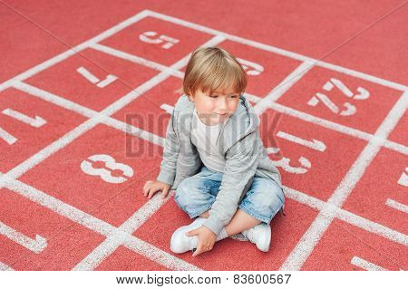 Adorable little boy resting on a schoolyard