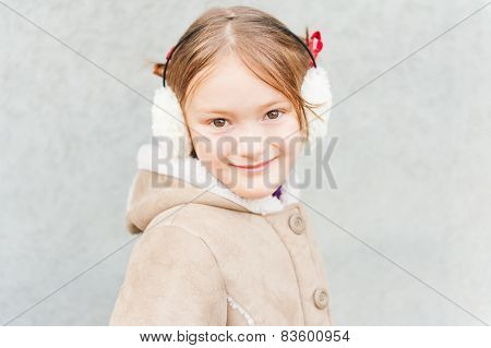 Outdoor portrait of a cute little girl wearing earmuffs and warm coat