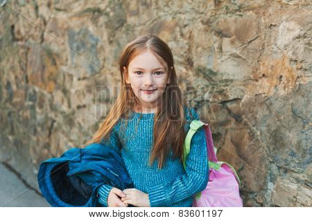 Adorable little girl of 7 years old ready to go to school, holding backpack and coat, wearing blue p