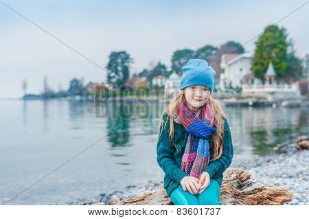 Pretty little girl resting by the lake on a cold cloudy day, wearing hat and scarf, green woolen pul