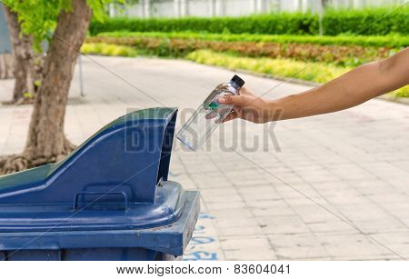 Hand throwing bottle in trash cans on street