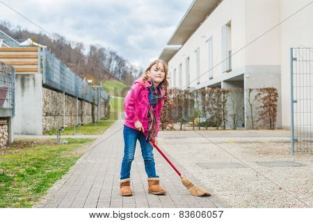 Cute little girl sweeping the backyard on a early spring day