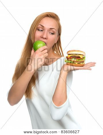 Woman Comparing Burger Sandwich In Hand And Green Apple