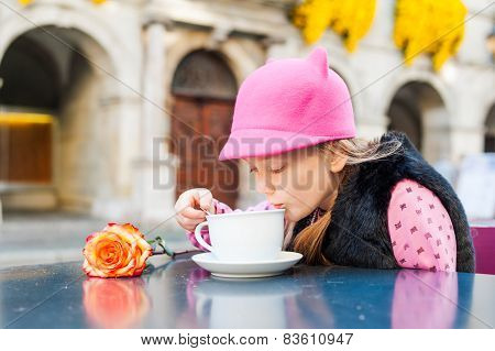 Outdoor portrait of a cute little girl drinking hot chocolate in a cafe on a nice sunny day, wearing