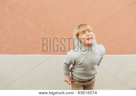Fashion portrait of adorable toddler boy, wearing sweatshirt