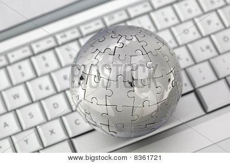 Metal puzzle globe on computer keyboard