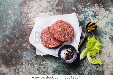 Raw Ground Beef Meat Burger Steak Cutlets And Seasonings On Metal Background