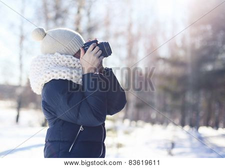 Child Photographer Takes Picture On The Digital Camera Outdoors In Winter Sunny Day