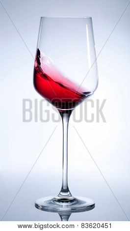 Red wine splashing in the elegant glass on gray