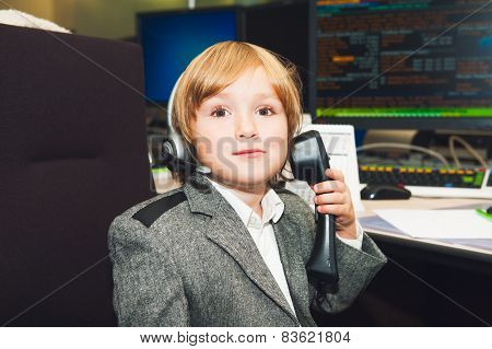 Adorable toddler boy spend the day at his parent's work in a trading room at the bank
