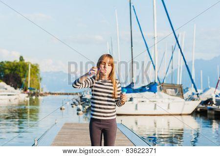 Cute little girl having fun on a nice sunny evening, outdoors