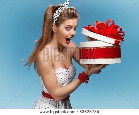 Portrait of happy woman opening gift box against blue background. Holidays, holiday, celebration, bi