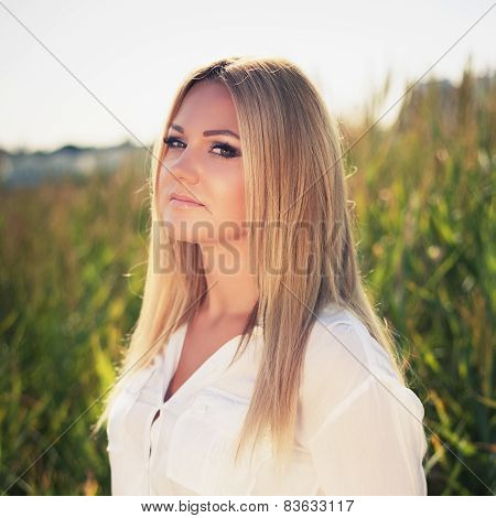 Young Beautiful Woman Poses In Green Thickets, Looks In The Camera