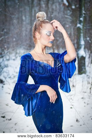 Lovely young lady in elegant blue dress posing in winter scenery, royal look. Fashionable blonde