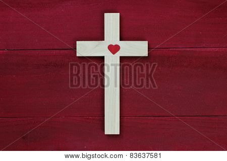 Wooden cross with heart hanging on antique red wood background