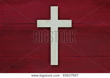 Wooden cross on antique red wooden background