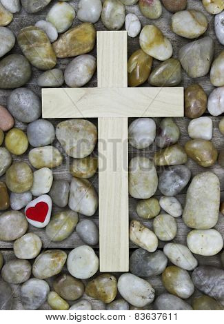 Wooden cross and red heart hanging on stone background