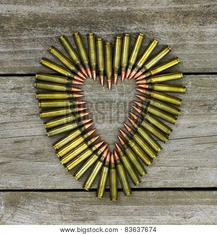 Heart-shaped bullets on rustic wood background
