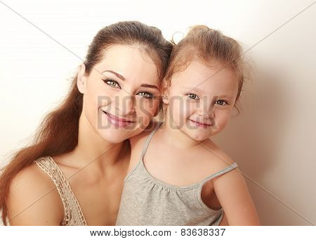 Beautiful Smiling Mother And Small Happy Daughter Cuddling