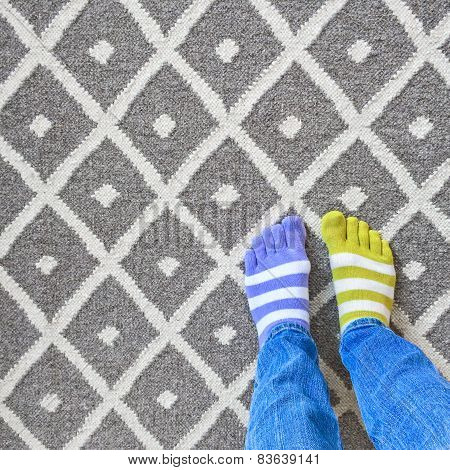 Legs In Mismatched Socks On Gray Carpet
