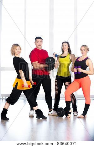 Group Of Sporty People Holding Dumbbells In Gym