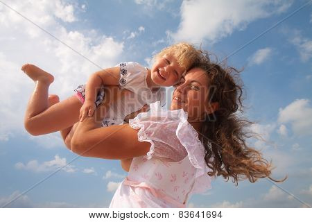 family, child and happiness concept - mother throws up her daughter
